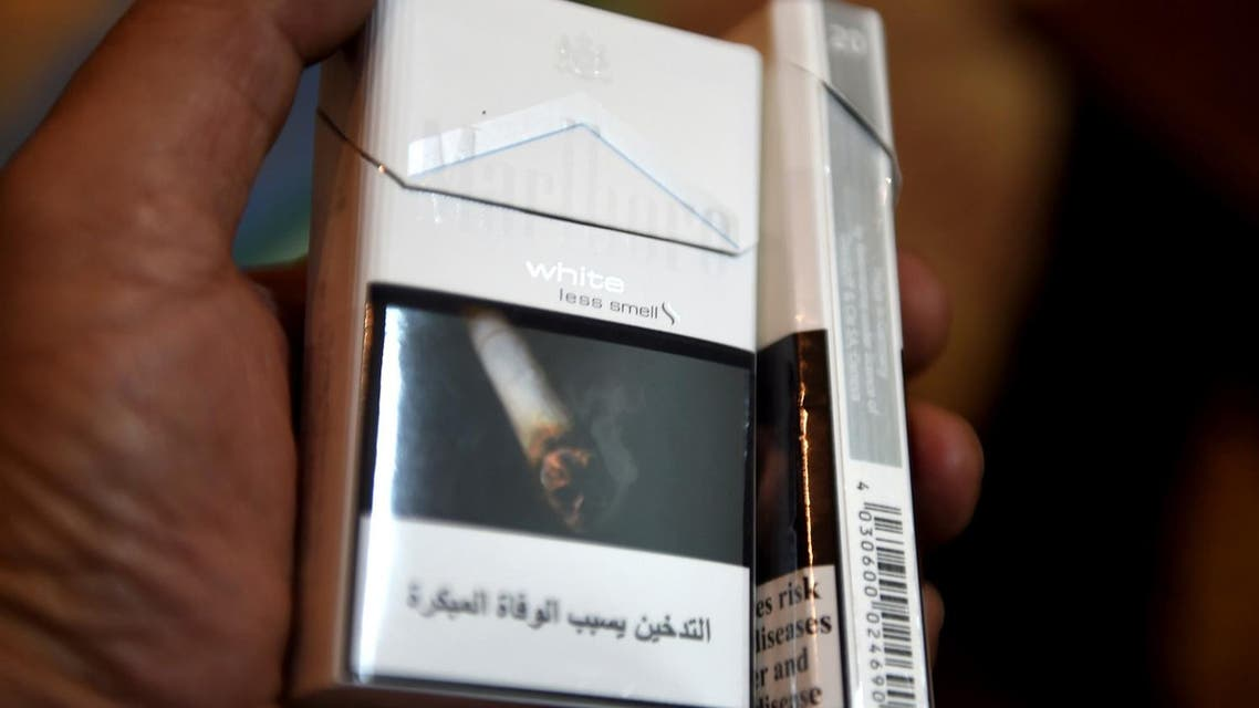 A man displays a pack of cigarettes outside a tobacco shop in Riyadh on June 11, 2017. (AFP)