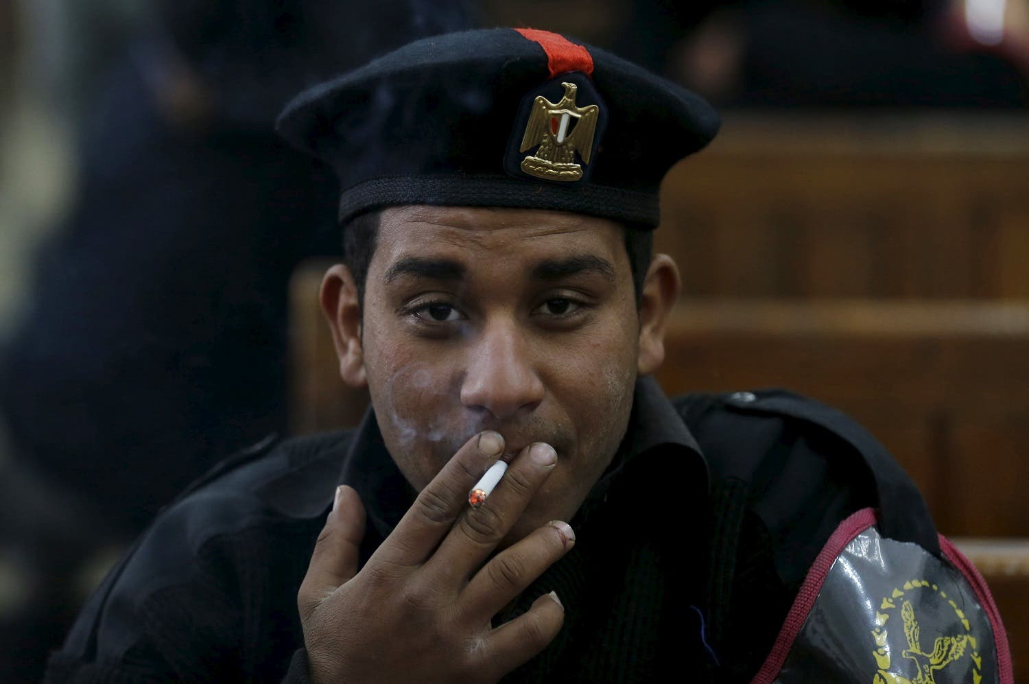 A policeman smokes cigarette in Cairo on April 11, 2015. (Reuters)