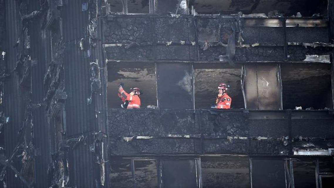 Members of the emergency services work inside the charred remains of the Grenfell apartment tower block in North Kensington. (Reuters)