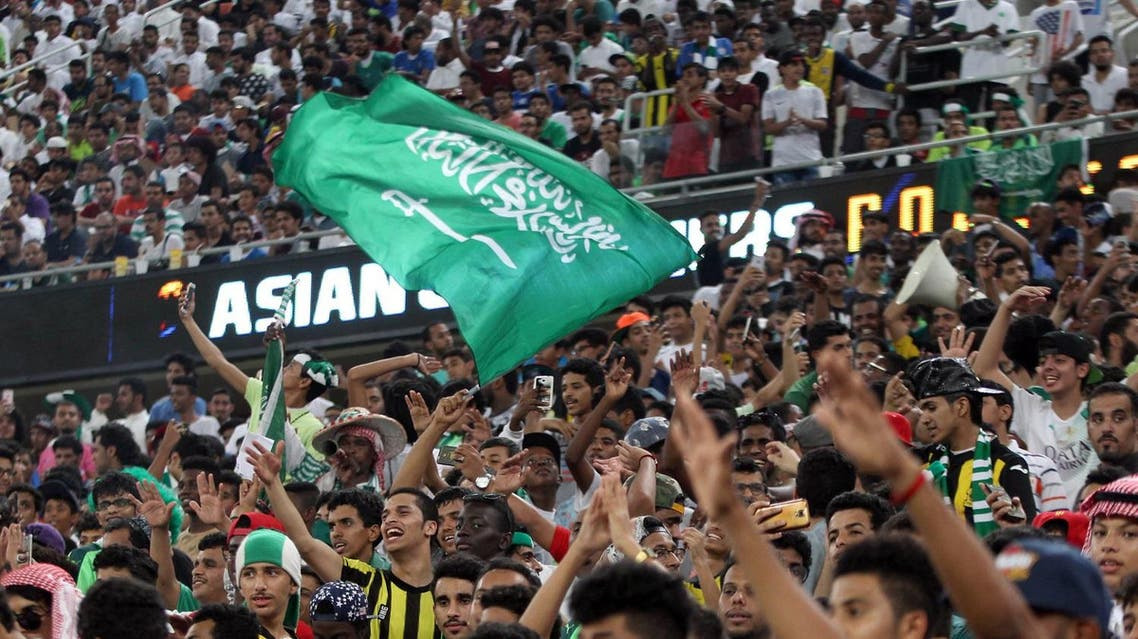 Saudi fans wave the national flag and chant during the 2018 World Cup qualifying football match between Saudi Arabia and United Arab Emirates at the King Abdullah Sports City stadium in Jeddah on October 11, 2016. (AFP)
