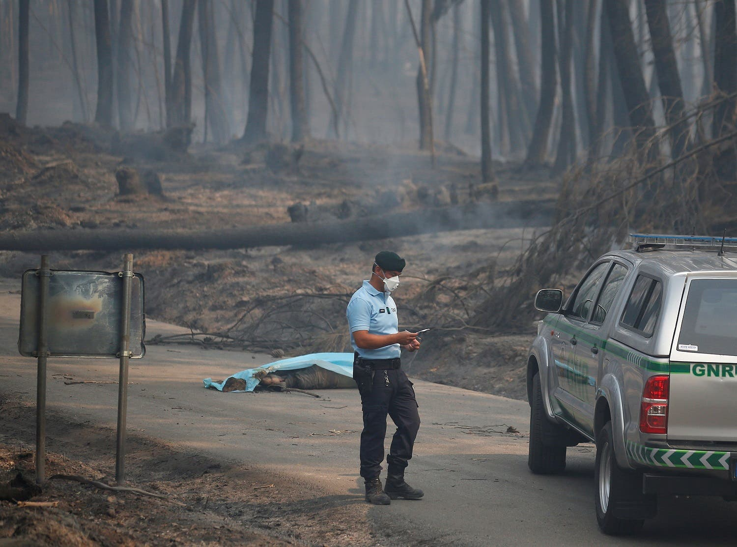 A policeman stands near a victim of a forest fire on the IC8 motorway near Pedrogao Grande, in central Portugal, June 18, 2017. (Reuters)