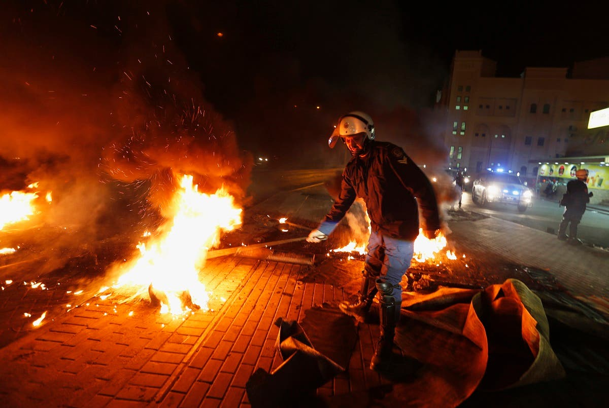 A riot police officer removes burning tyres from the highway set up by anti-government protesters in the village of Diraz west of Manama April 11, 2013. (Reuters)