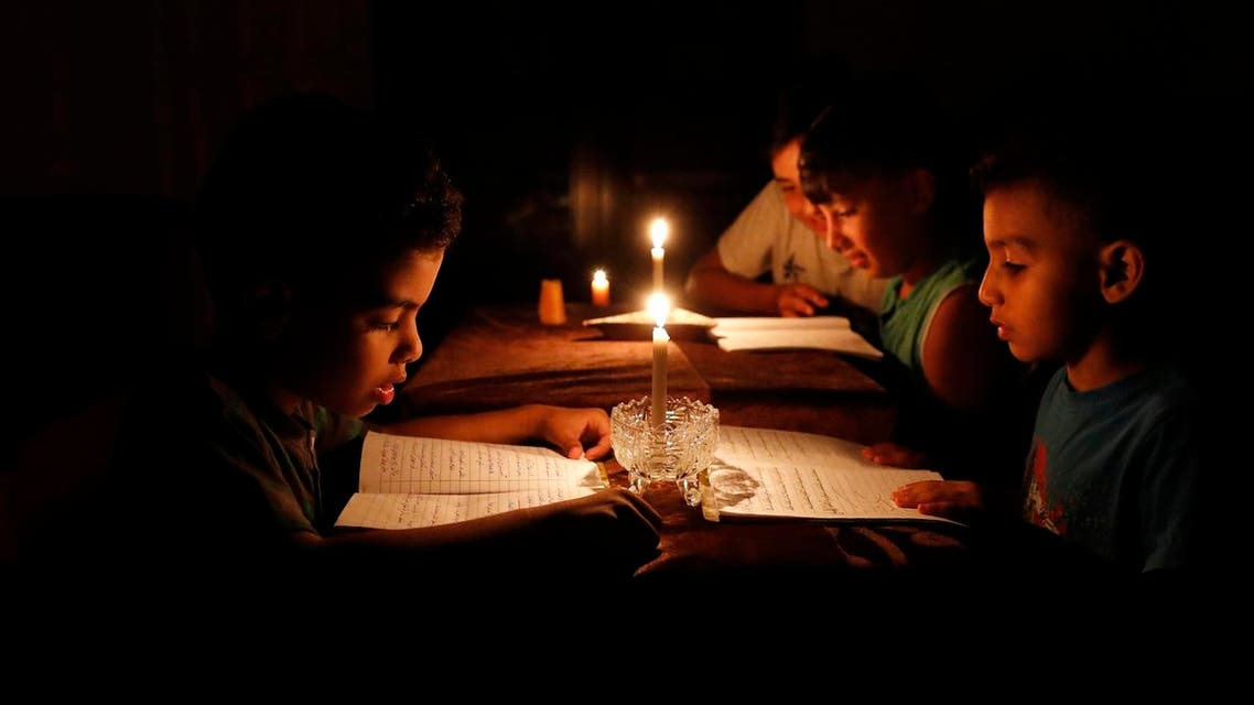"""A picture taken on June 13, 2017, shows Palestinian children at home reading books by candle light due to electricity shortages in Gaza City. Israeli Prime Minister Benjamin Netanyahu said he was not seeking an """"escalation"""" in the Gaza Strip after his government moved to reduce electricity supplies to the Hamas-run enclave. (afp)"""