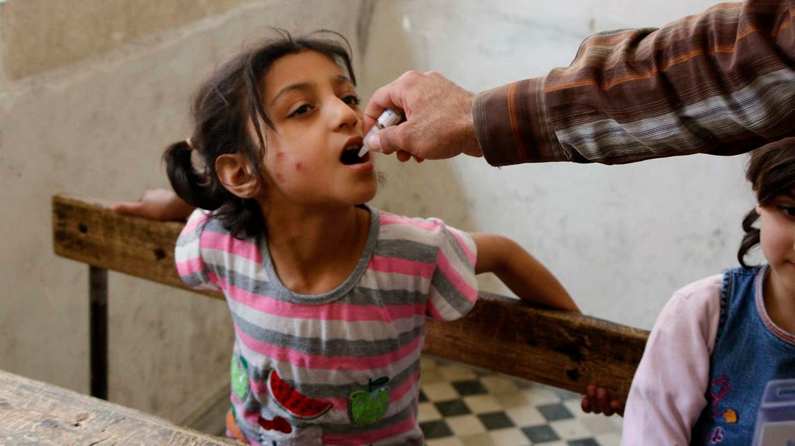 An activist health worker administers a polio vaccination to a child in Aleppo May 4, 2014. REUTERS/Hosam Katan (SYRIA - Tags: POLITICS CIVIL UNREST CONFLICT HEALTH)