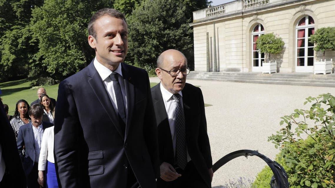 French president Emmanuel Macron (L) leaves with French Foreign Affairs Minister Jean-Yves Le Drian for a cabinet meeting after they posed for a family photo at the Elysee Palace in Paris on June 22, 2017. (AFP)