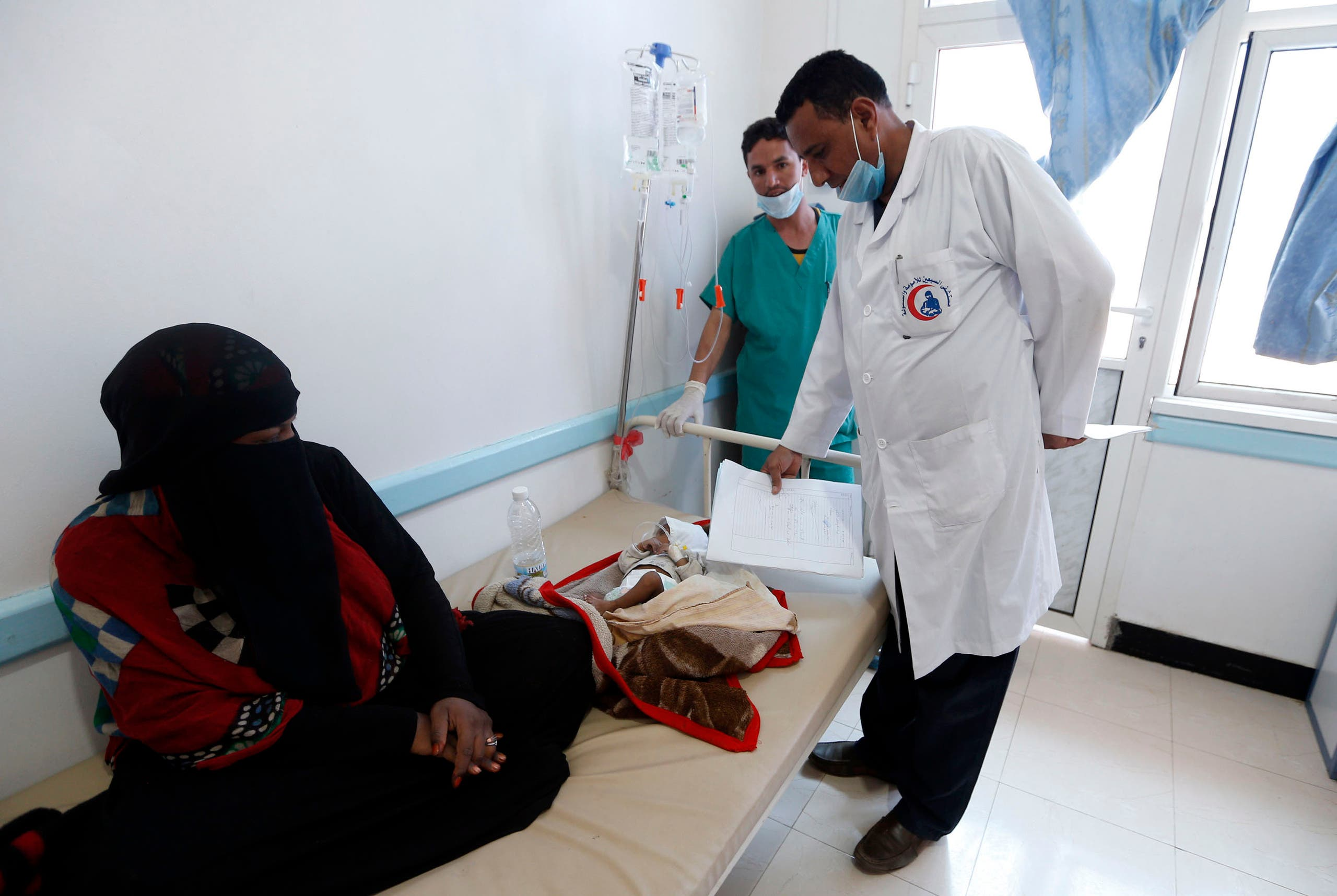 A Yemeni mother sits near her child suspected of being infected with cholera receiving treatment at a hospital in Sanaa on May 25, 2017. (AFP)