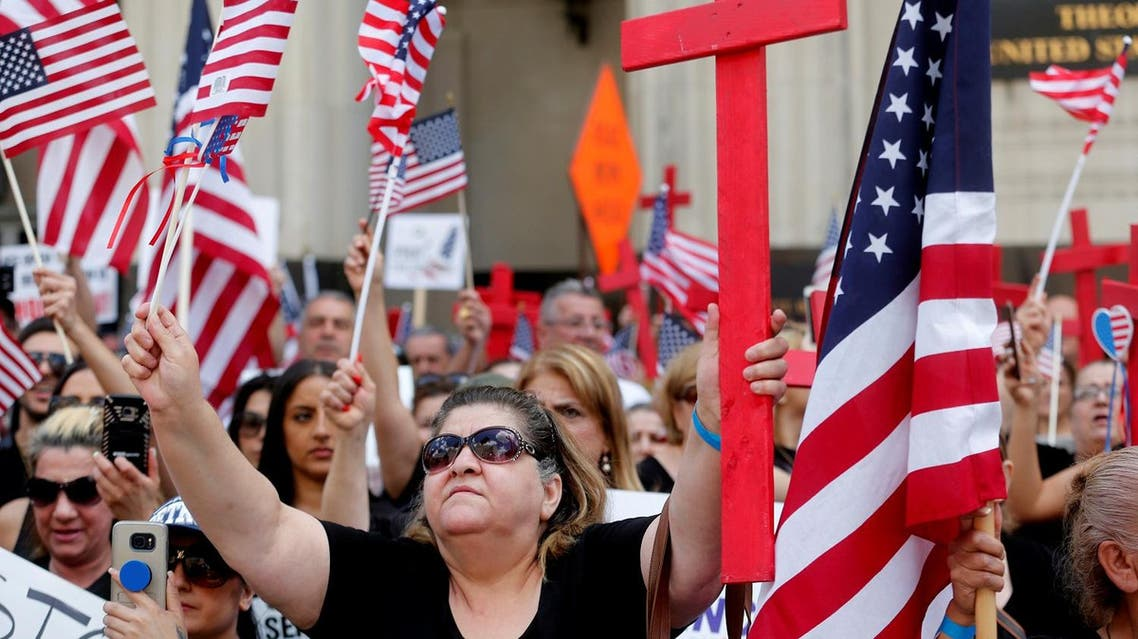 Protesters rally outside the federal court just before a hearing to consider a class-action lawsuit filed on behalf of Iraqi nationals facing deportation, in Detroit, Michigan, US, June 21, 2017. (Reuters)