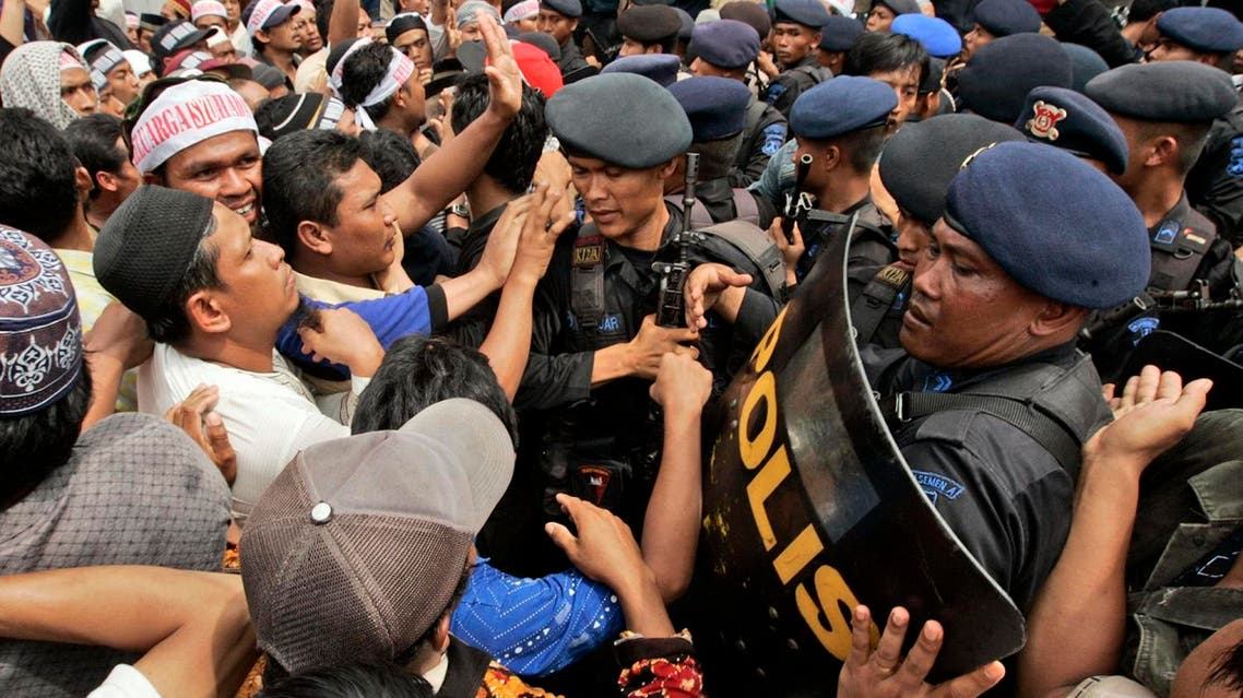 Supporters of Bali bombers Amrozi Nurhasyim and Ali Ghufron scuffle with riot police during their funeral in Lamongan, East Java, Indonesia, Sunday, Nov. 9, 2008.