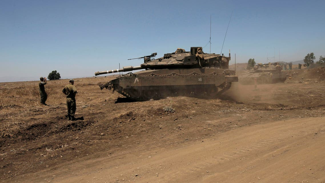 Israeli soldiers direct a Merkava tank stationed in the Israeli annexed Golan Heights near the Quneitra crossing with Syria on July 26, 2016.