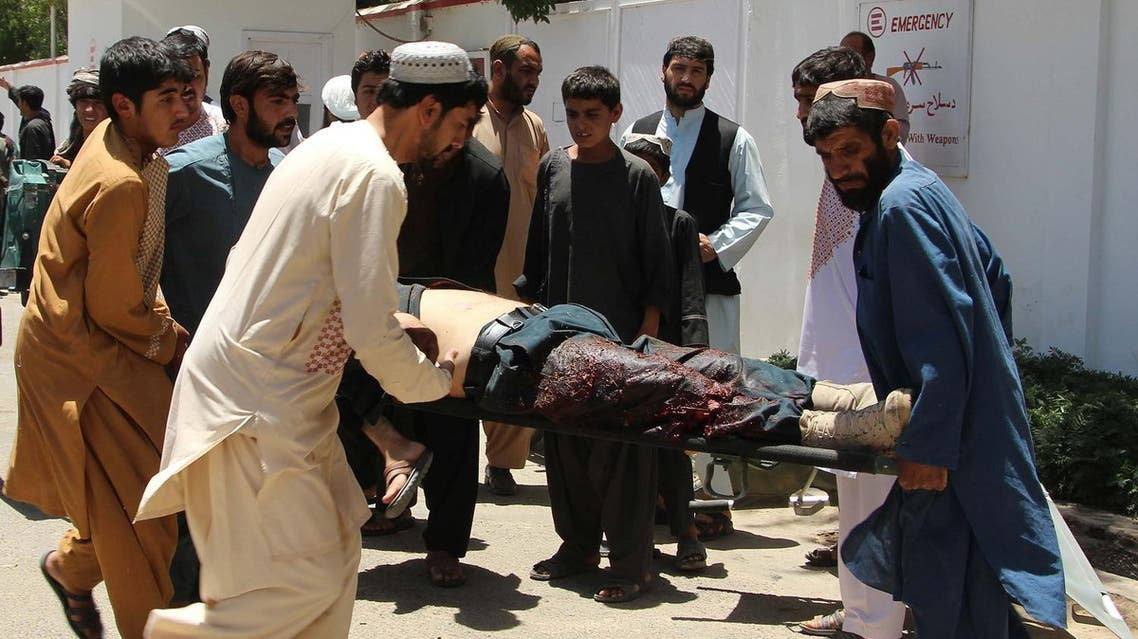 Afghan men carry a victim of a powerful car bomb in Lashkar Gah, the capital of Helmand province, on June 22, 2017. Twenty people were killed June 22 when a powerful car bomb struck a bank in Afghanistan's Lashkar Gah city as government employees were queueing to withdraw salaries, the latest bloody attack during the holy month of Ramadan. (AFP)