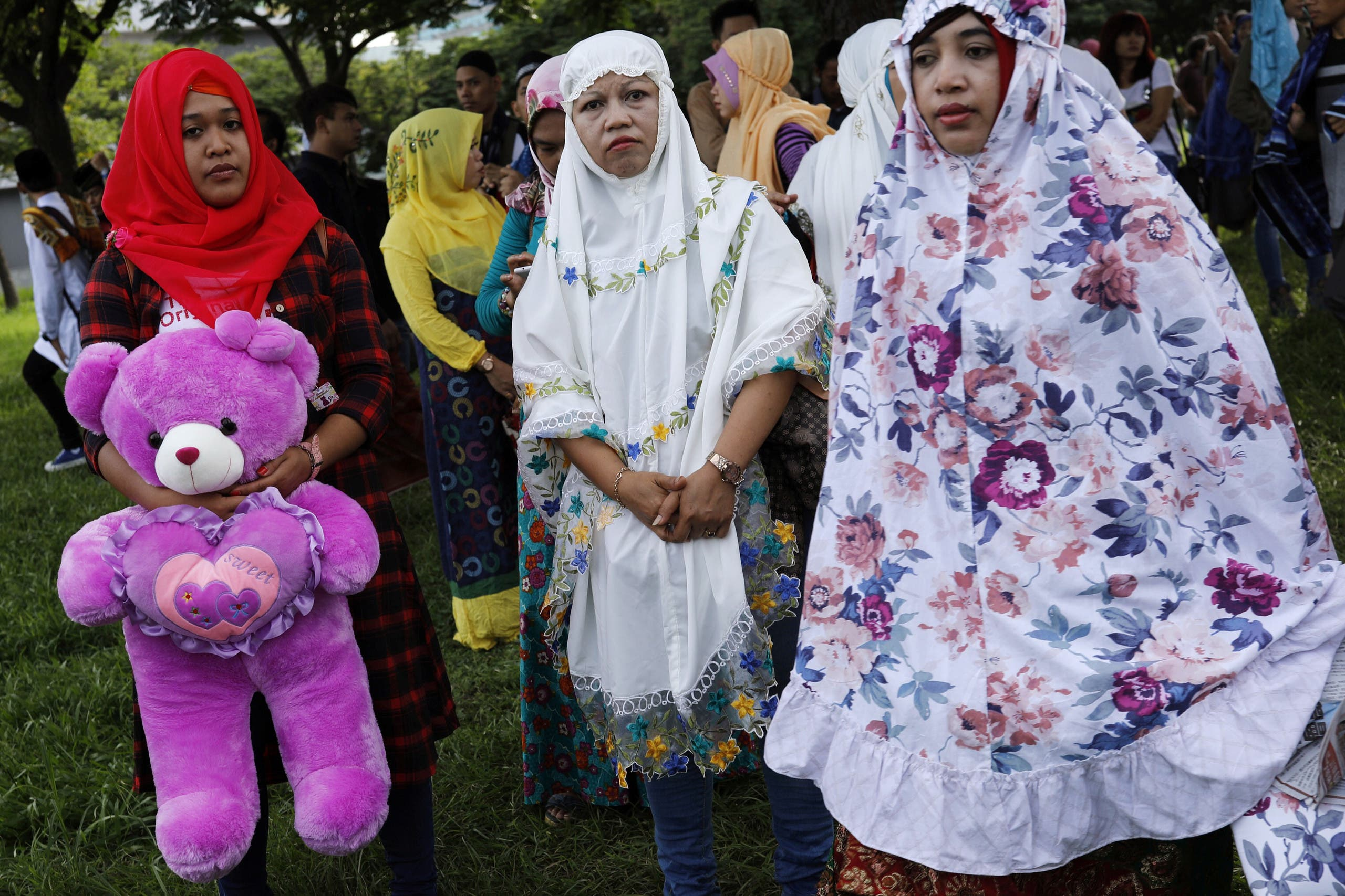 A Muslim woman hold a doll as she attend Eid al-Fitr prayers to mark the end of the holy fasting month of Ramadan in Taipei , Taiwan June 25, 2017. REUTERS/Tyrone Siu
