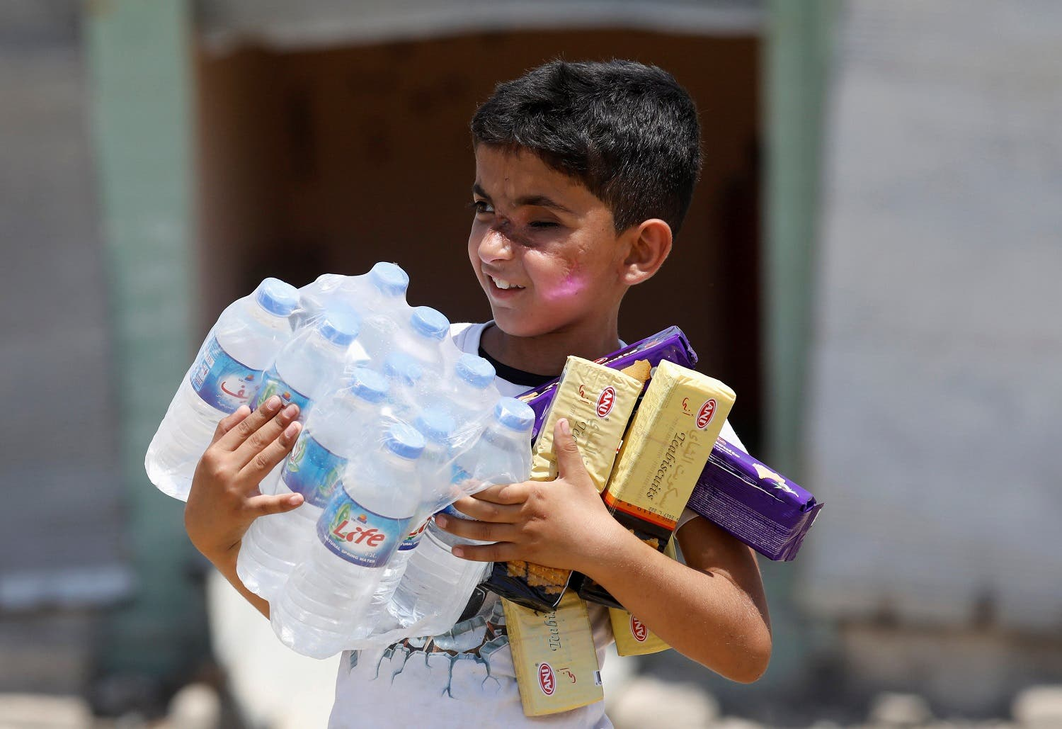 A boy carries bottles of water and biscuits given by an aid organization during the first day of Eid-al Fitr celebration in West Mosul, Iraq June 25, 2017. (Reuters)