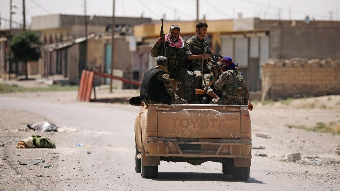 Syrian Democratic Forces (SDF) fighters ride on a pick-up truck along a street in Raqqa's western neighbourhood of Jazra, Syria June 11, 2017. REUTERS/Rodi Said