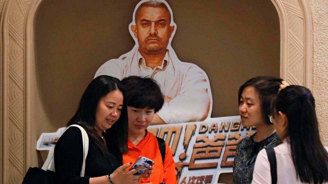 """In this May 22, 2017 photo, a Chinese woman browses a photo which she took with her friends with a poster of blockbuster film """"Dangal,"""" back, at a cinema in Beijing. (AP)"""