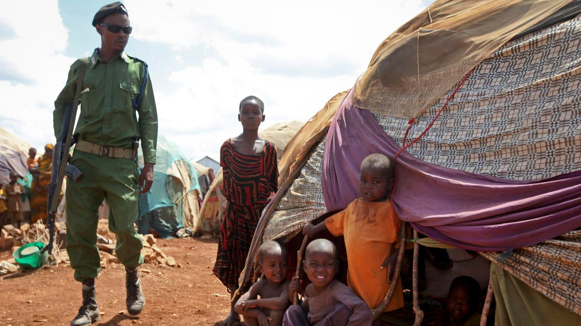 In this photo taken Saturday, March 25, 2017, a Somali policeman walks past as newly displaced Somali children stand outside their makeshift shelter at a camp in Baidoa, Somalia. AP
