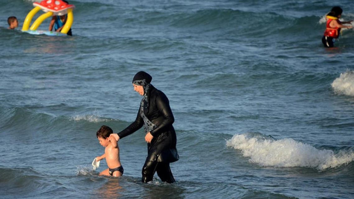 A Burkini-clad woman with a child take to the waters at the beach. (Supplied)
