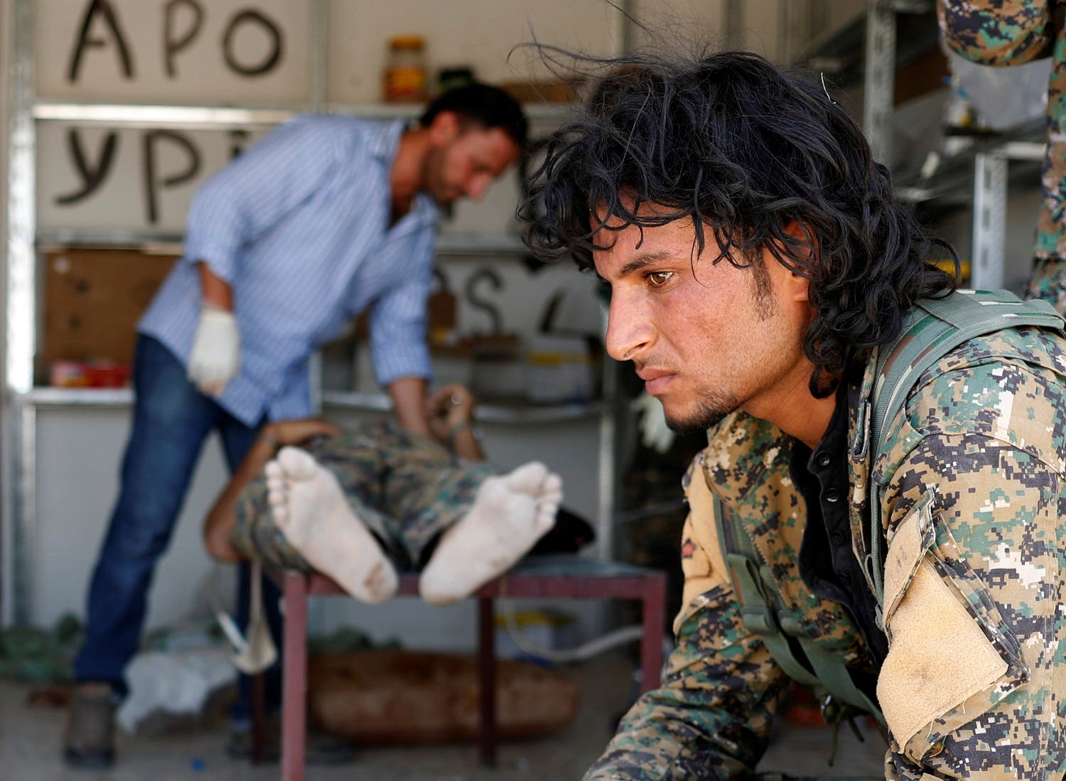 A Syrian Democratic Forces fighter sit as medics treat his comrades injured by sniper fired by ISIS militants in a field hospital in Raqqa, Syria June 28, 2017. (Reuters)