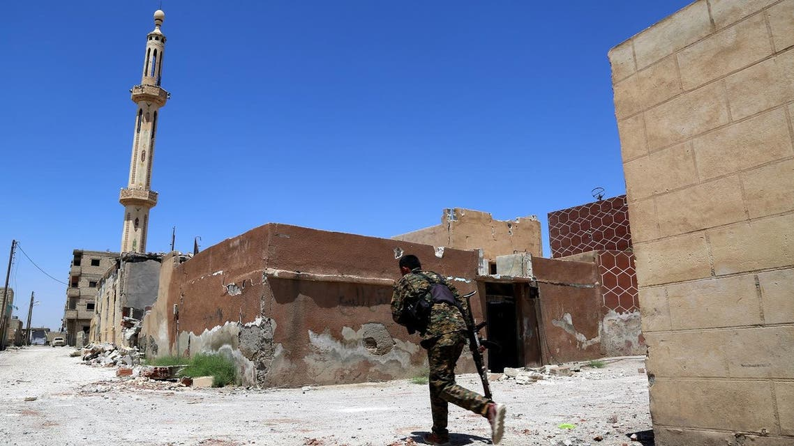 A member of the Syrian Democratic Forces (SDF) crosses a street on June 27, 2017 in the suburb of Dariya on the western city limits of Raqqa after the area was seized by SDF from the ISIS. (AFP)