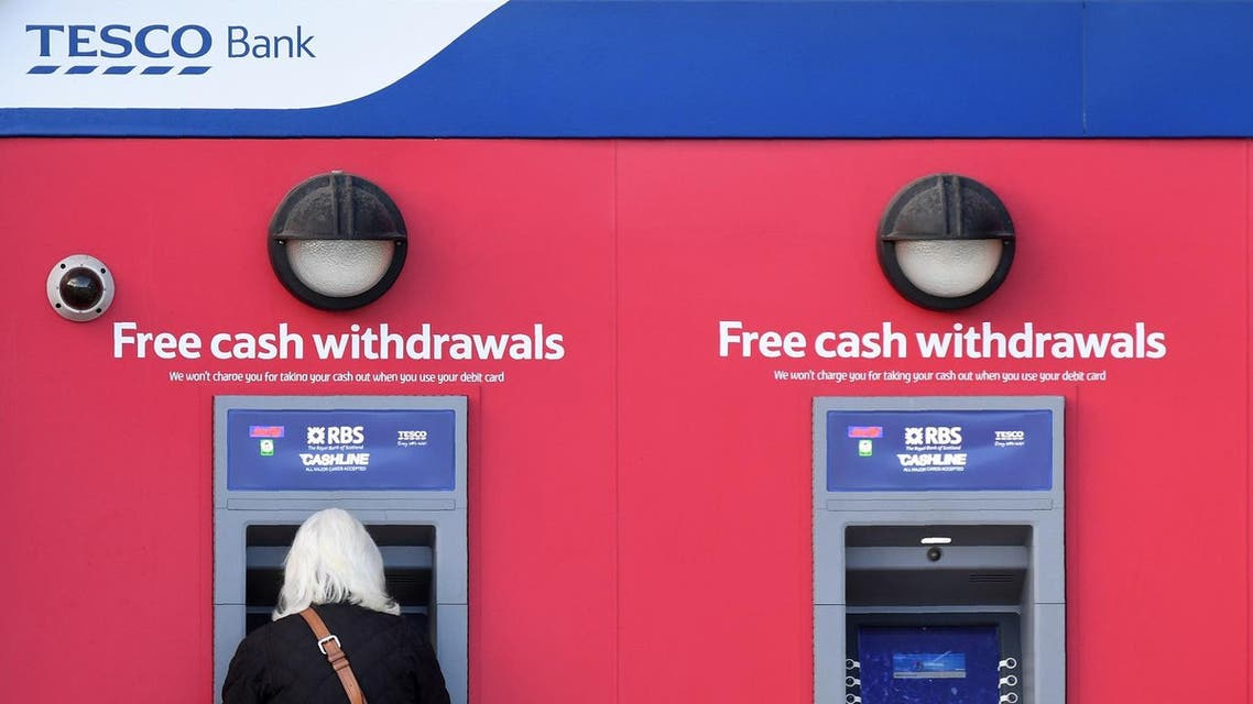A customer uses an RBS branded automated teller machine (ATM), at a Tesco Bank cash point, in Liverpool, north west England, on November 7, 2016. (AFP)