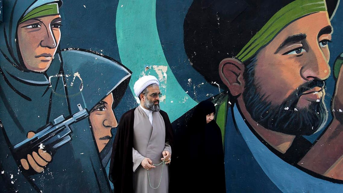 A cleric and his wife stand in front of a mural showing depicting members of paramilitary Basij during an annual pro-Palestinian rally marking Al-Quds Day in Tehran on June 23, 2017. (AP)