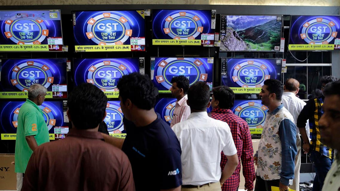 People look at televisions inside an electronics shop, a day ahead of the implementation of the nationwide Goods and Services Tax (GST) in Mumbai, on June 30, 2017. (AP)