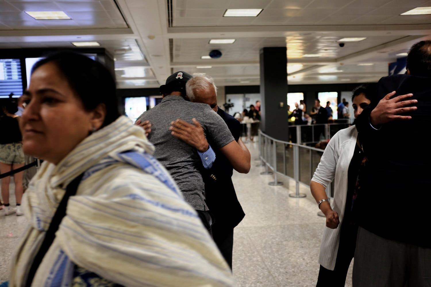 International passengers embrace family members as they arrive at Washington Dulles International Airport on June 29, 2017. (Reuters)