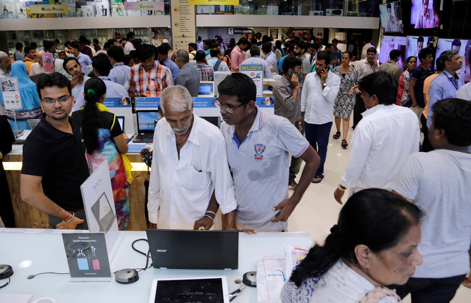 Customers crowd an electronics shop, a day ahead of the implementation of the nationwide Goods and Services Tax (GST) in Mumbai. (AP)