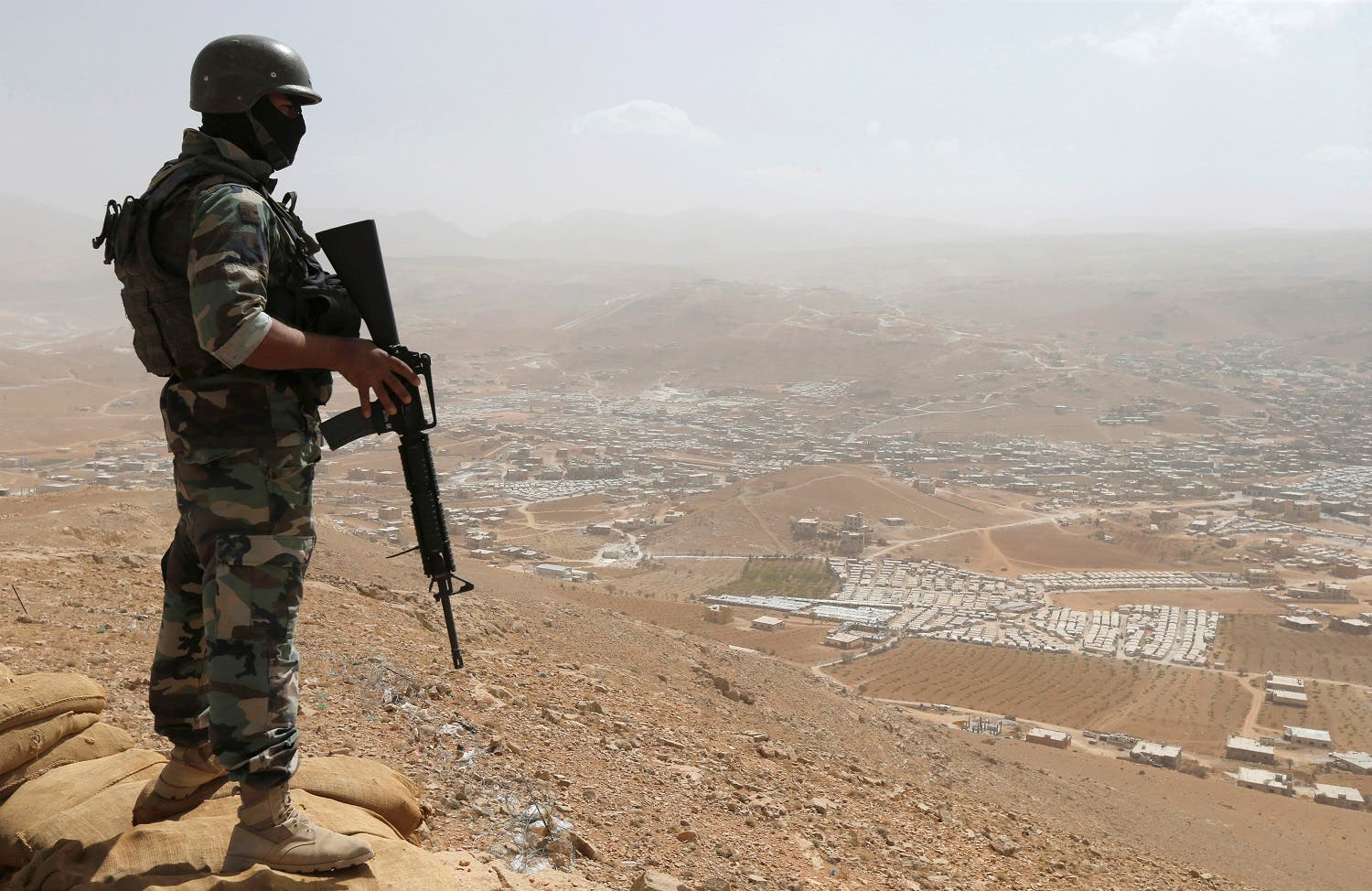 A Lebanese soldier carries his weapon as he stands on sandbags at an army post in the hills above the Lebanese town of Arsal, near the border with Syria, Lebanon September 21, 2016. Picture taken September 21, 2016. REUTERS/Mohamed Azakir TPX IMAGES OF THE DAY