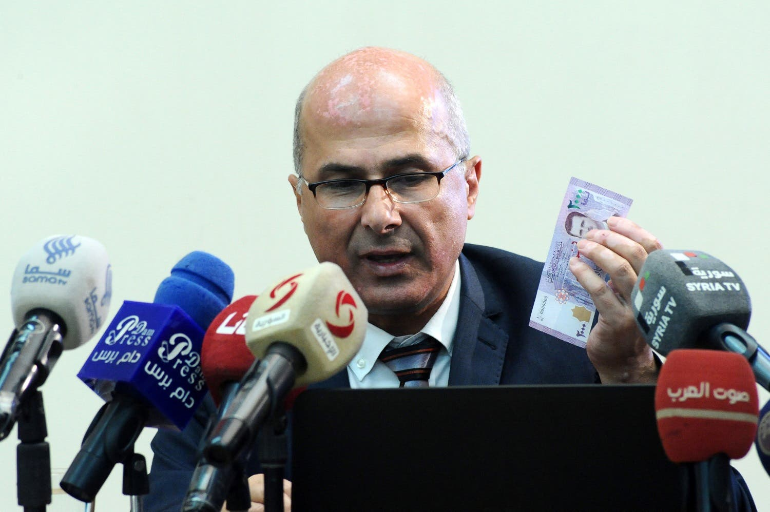 Central Bank of Syria governor Duraid Durgham speaks during a news conference as he holds the new Syrian 2,000-pound banknote that went into circulation on July 2, 2017, Syria.  (Reuters)