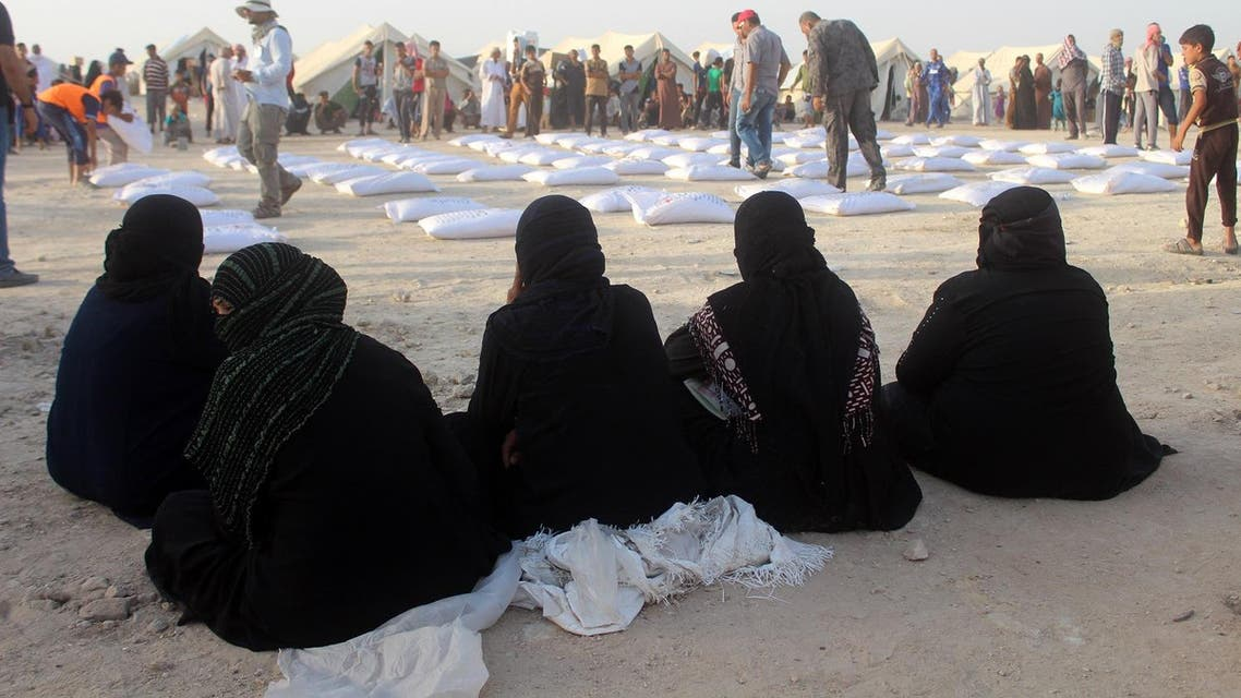 Iraqi women displaced from Ramadi, sit and wait to receive aid from the International Committee of the Red Cross (ICRC) at a makeshift camp where they are taking shelter in Habbaniyah, just east of the capital of Iraq's Anbar province. (AFP)