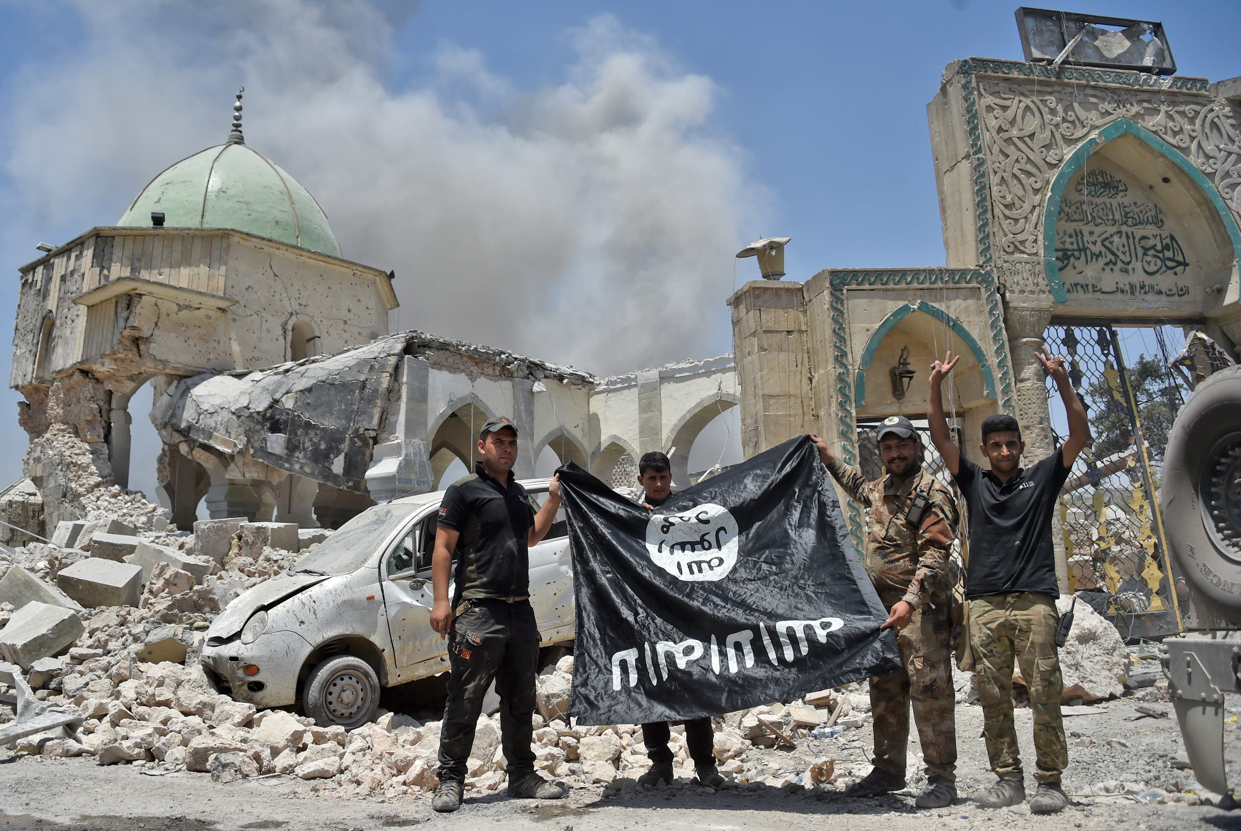 A member of the Iraqi Counter-Terrorism Service (CTS) raises the victory gesture as others hold upside-down the black flag of the Islamic State (IS) group, outside the destroyed Al-Nuri Mosque in the Old City of Mosul, after the area was retaken from IS, on June 30, 2017.(AFP)
