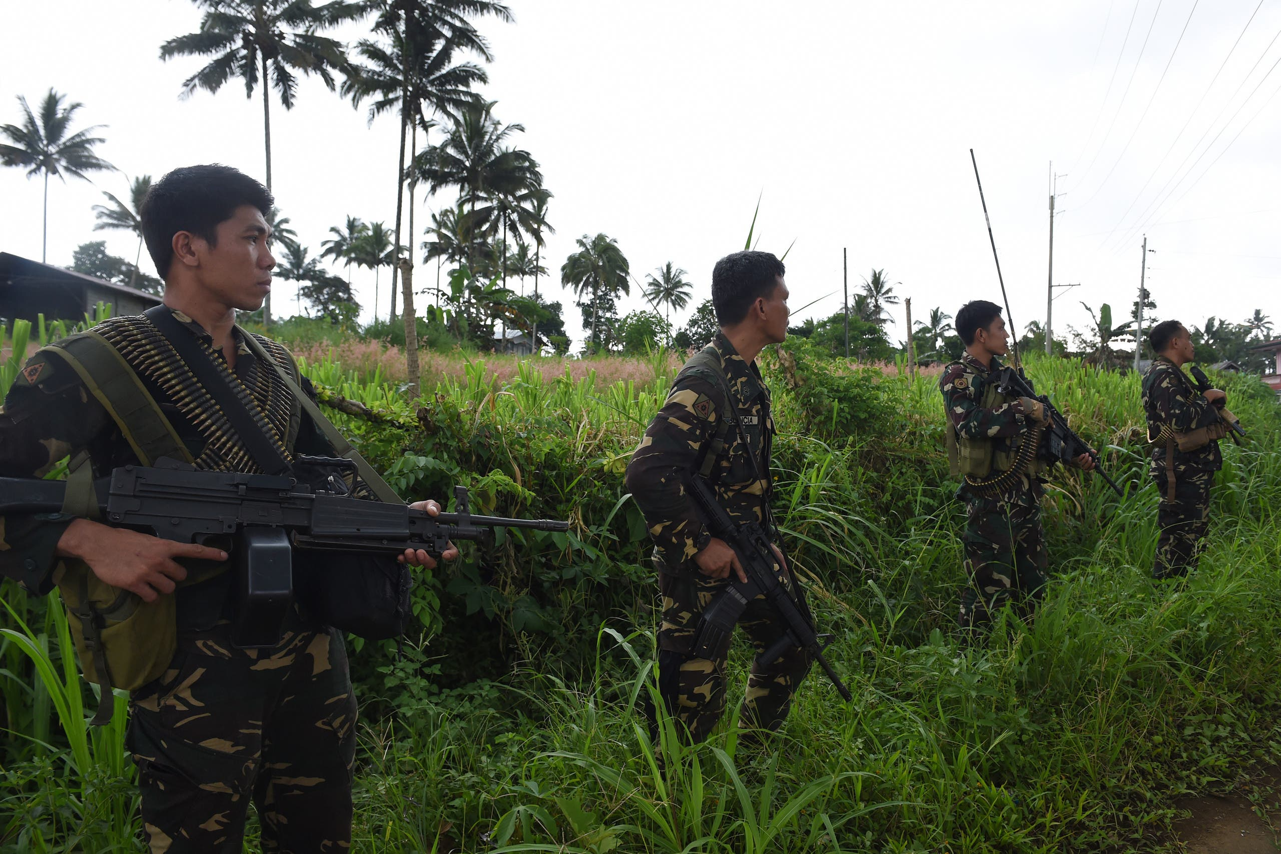 Philippine soldiers secure a road as they provide security for a retrieval operation of dead civilians in the outskirts of Marawi on the southern island of Mindanao on June 28, 2017. (AfP)