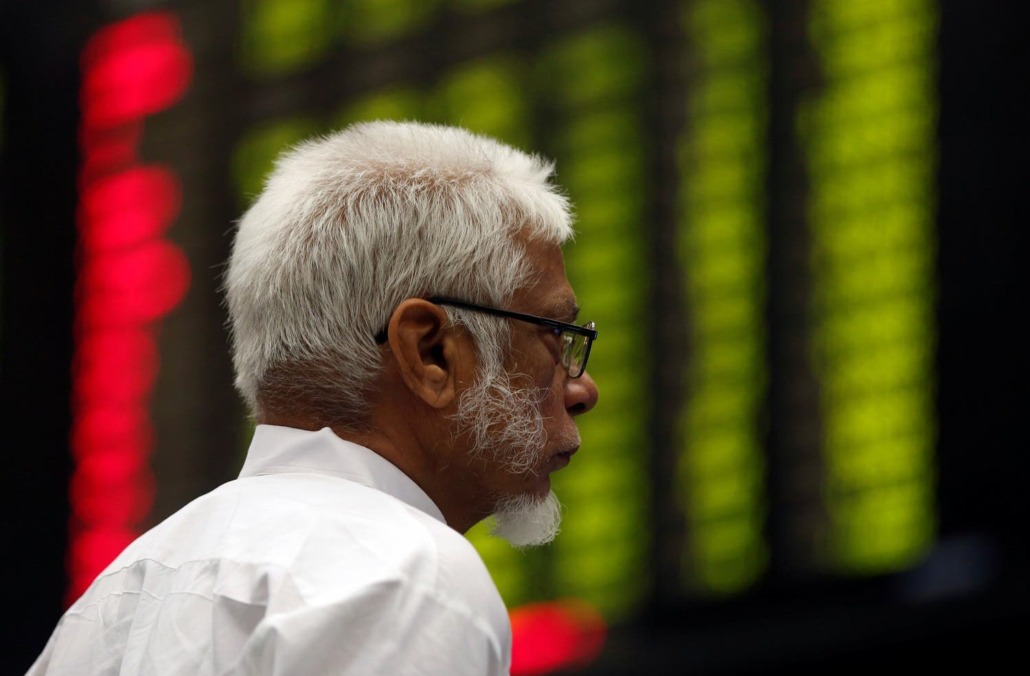 A man monitors an electronic board displaying share market prices during a trading session in the halls of Pakistan Stock Exchange (PSX) in Karachi, Pakistan, on June 12, 2017. (Reuters)