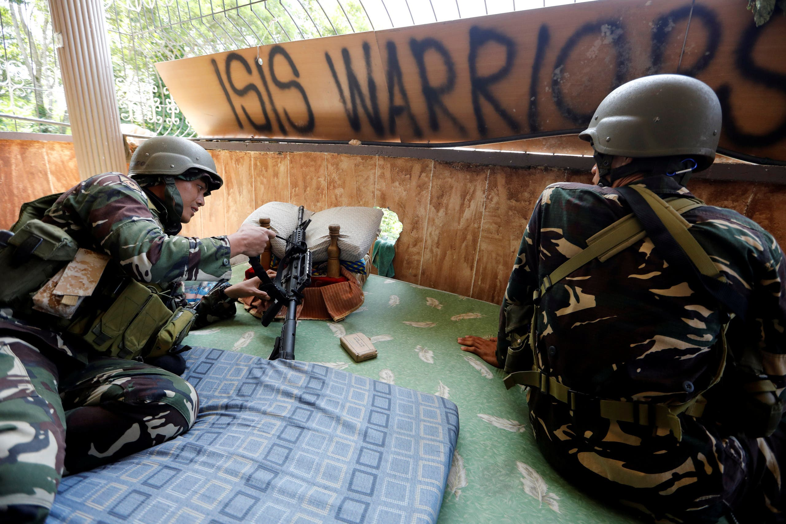 Filipino soldiers lie on a mattress at their combat position in a house as government troops continue their assault against insurgents from the Maute group in Marawi city, Philippines July 1, 2017. Reuters