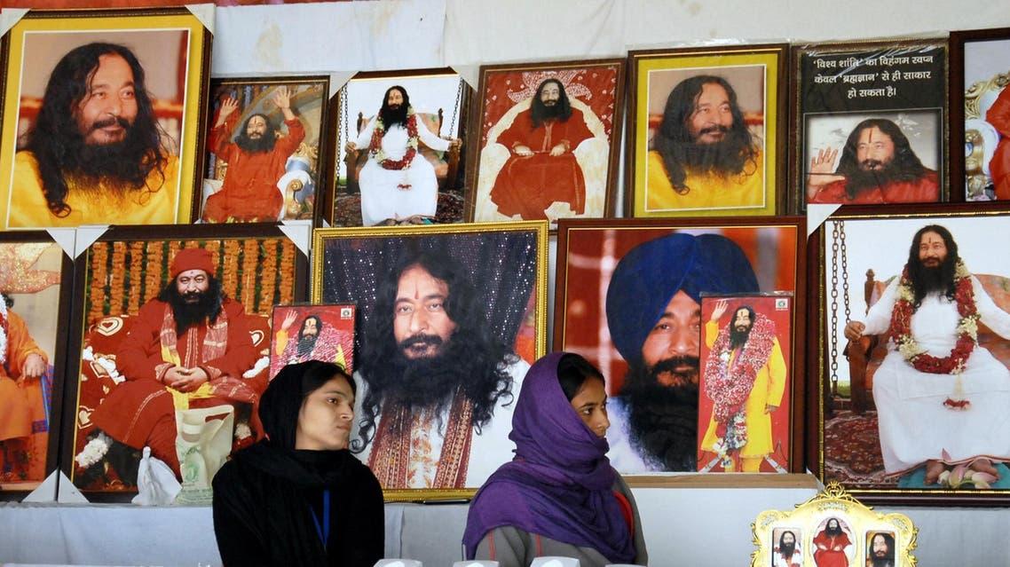 Indian followers of deceased guru Ashutosh Maharaj Divya Jyoti Jagriti Sansthaan sit front posters bearing his image at a stall during a congregation at his ashram 30kms from Jalandhar on December 14, 2014. (File photo: AFP)