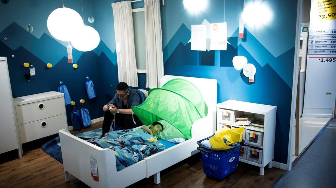 A father with his child escaping the summer heat by letting him sleep in a bed in a Ikea store in downtown Shanghai. (AFP)