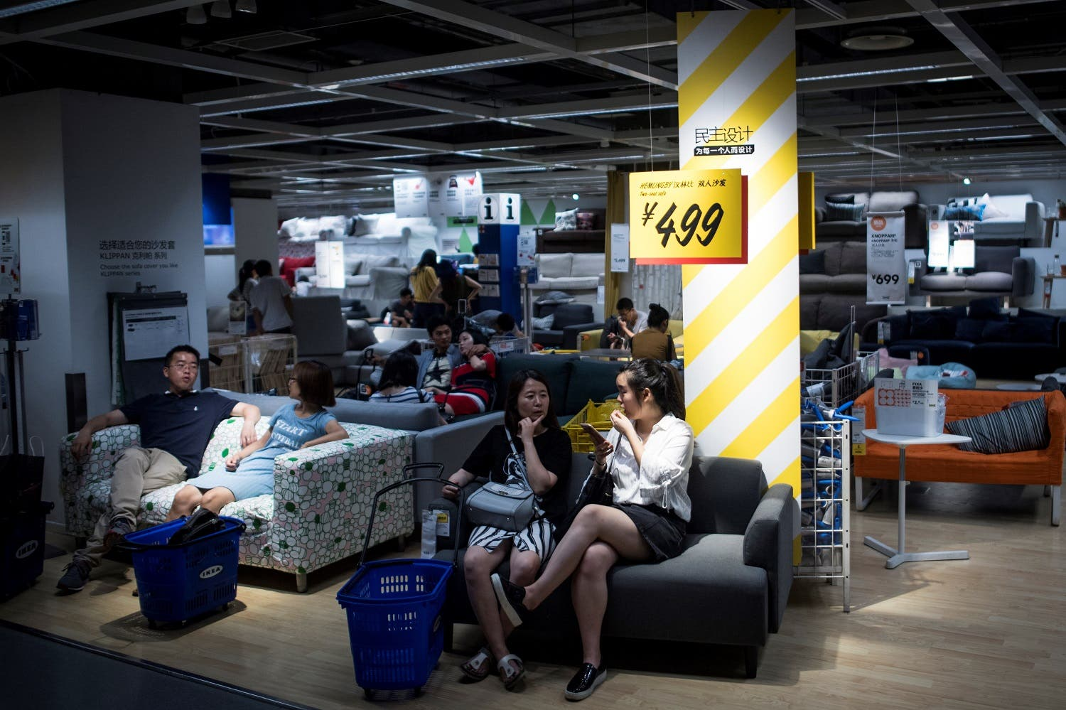 People escaping the summer heat by relaxing on a sofa in a Ikea store in downtown Shanghai. (AFP)
