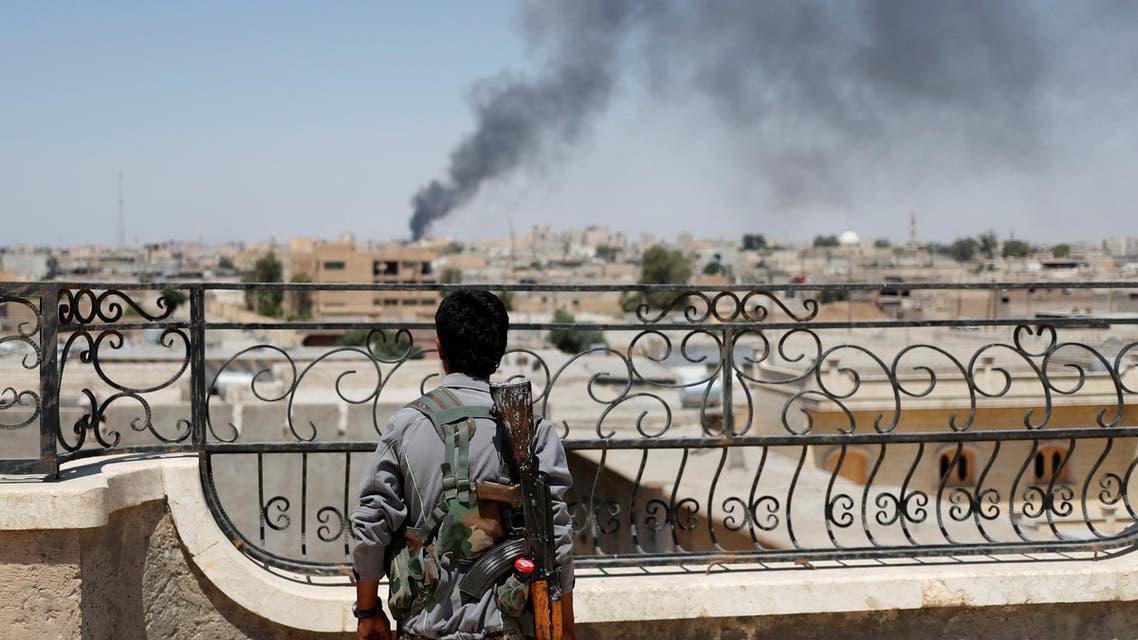مقاتل من وحدات الحماية ينظر إلى غارة شنها التحالف الدولي في الرقة