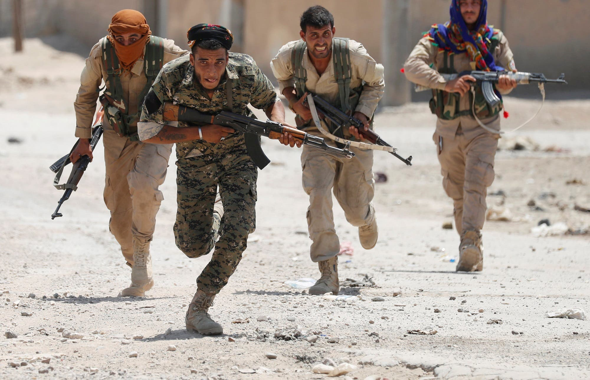 Kurdish fighters from the People's Protection Units (YPG) run across a street in Raqqa, Syria July 3, 2017. (Reuters)