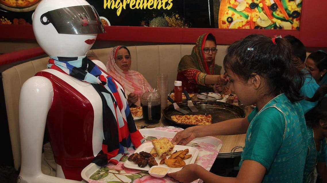 In this photograph taken on July 4, 2017, a young customer picks up food from a tray carried by a robot waitress at a pizza restaurant in Multan. (AFP)