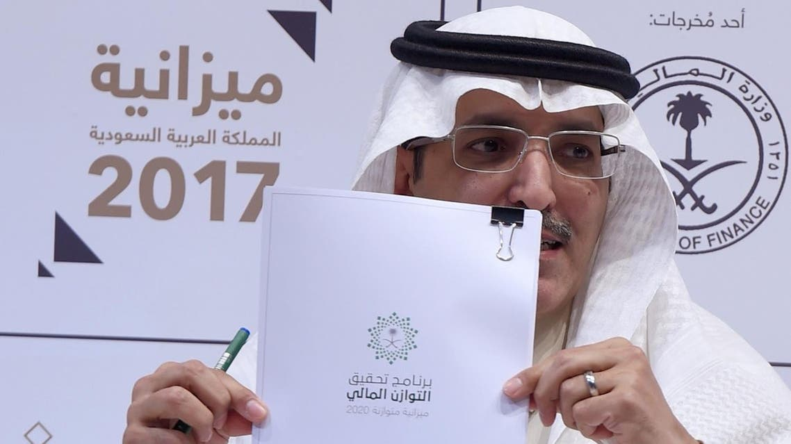 Saudi Finance Minister Mohammed Al-Jadaan shows documents during a press conference to unveil the country's national budget for 2017. (AFP)