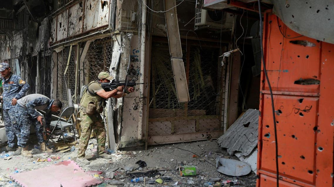 A member of the Emergency Response Division opens fire against ISIS militants in the Old City of Mosul, on July 7, 2017. (Reuters)