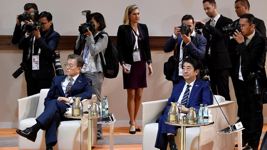 """South Korea's President Moon Jae-in (left) and Japan's Prime Minister Shinzo Abe sit at the start at the start of the """"retreat meeting"""" on the first day of the G20 summit in Hamburg, Germany, on July 7, 2017. (Reuters)"""