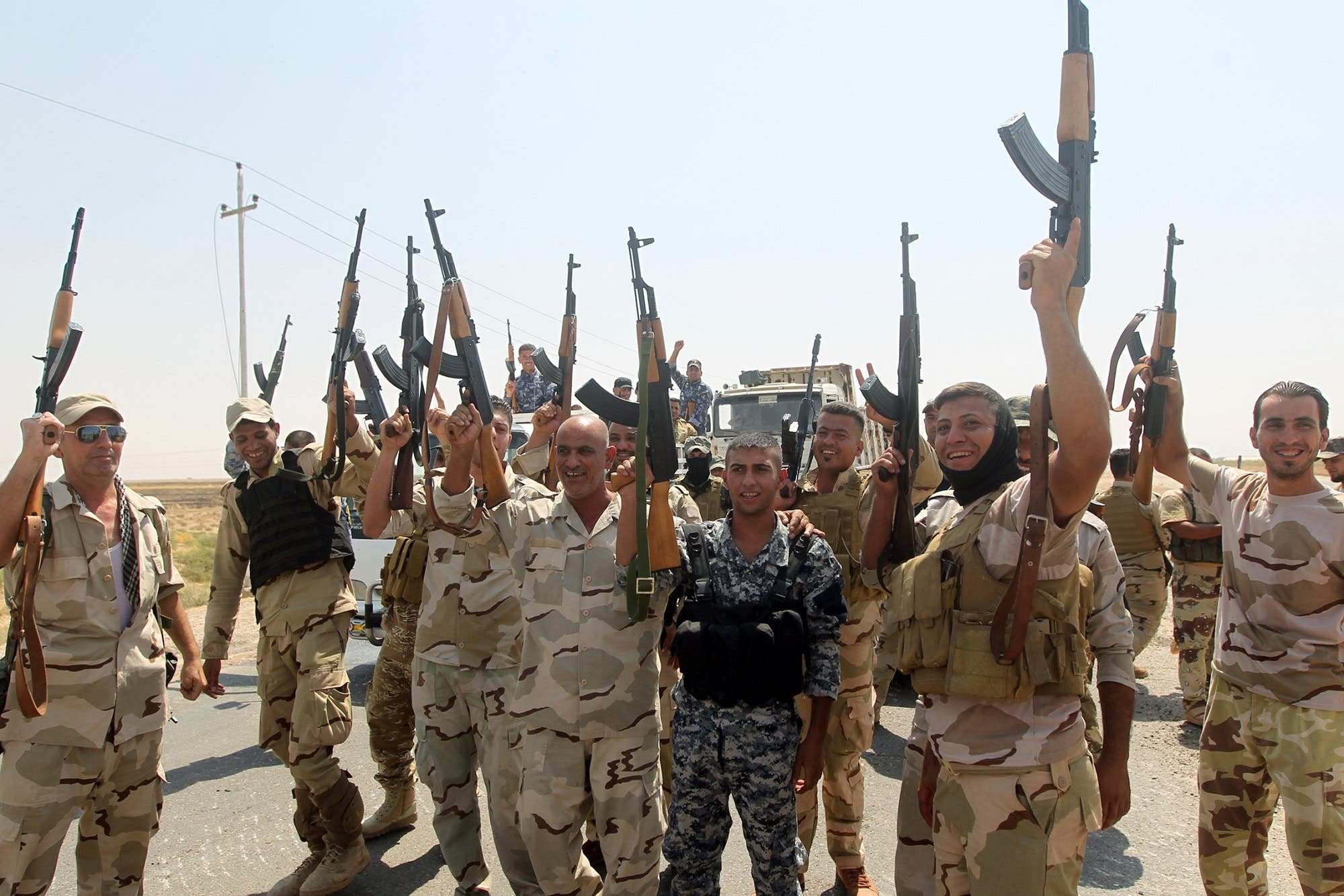 Iraqi members of Badr Organization raise up their weapons as they celebrate on September 1, 2014 near Diyala province after Iraqi forces broke through to the Shiite town of Amerli. (AFP)