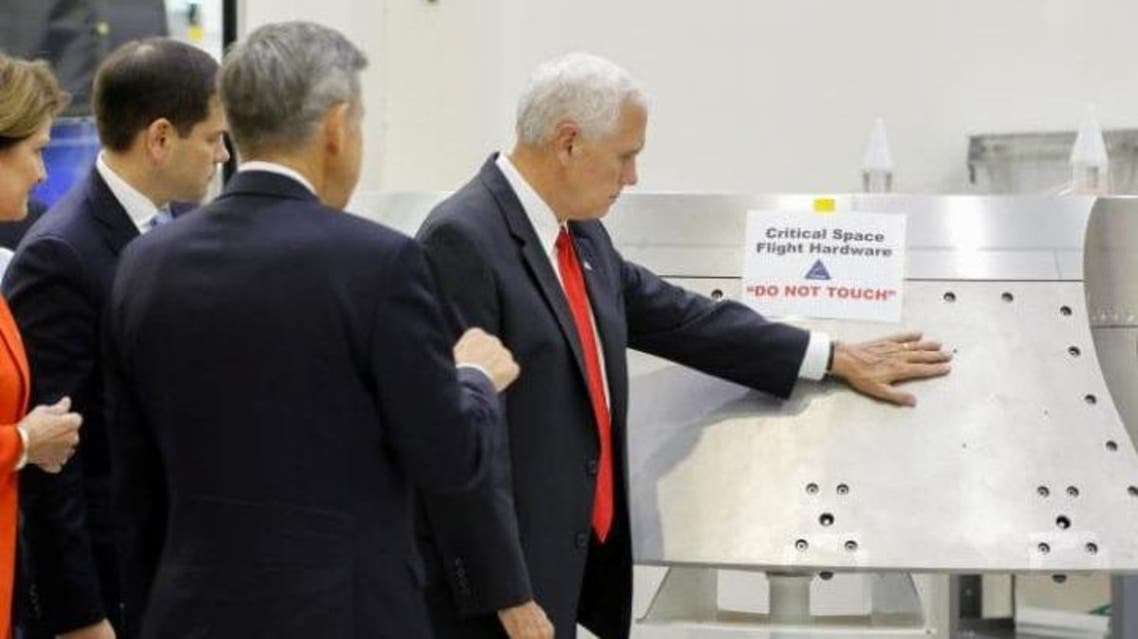 """U.S. Vice President Mike Pence touches a piece of hardware with a warning label """"Do Not Touch"""" at Kennedy Space Center in Florida Credit: Reuters"""