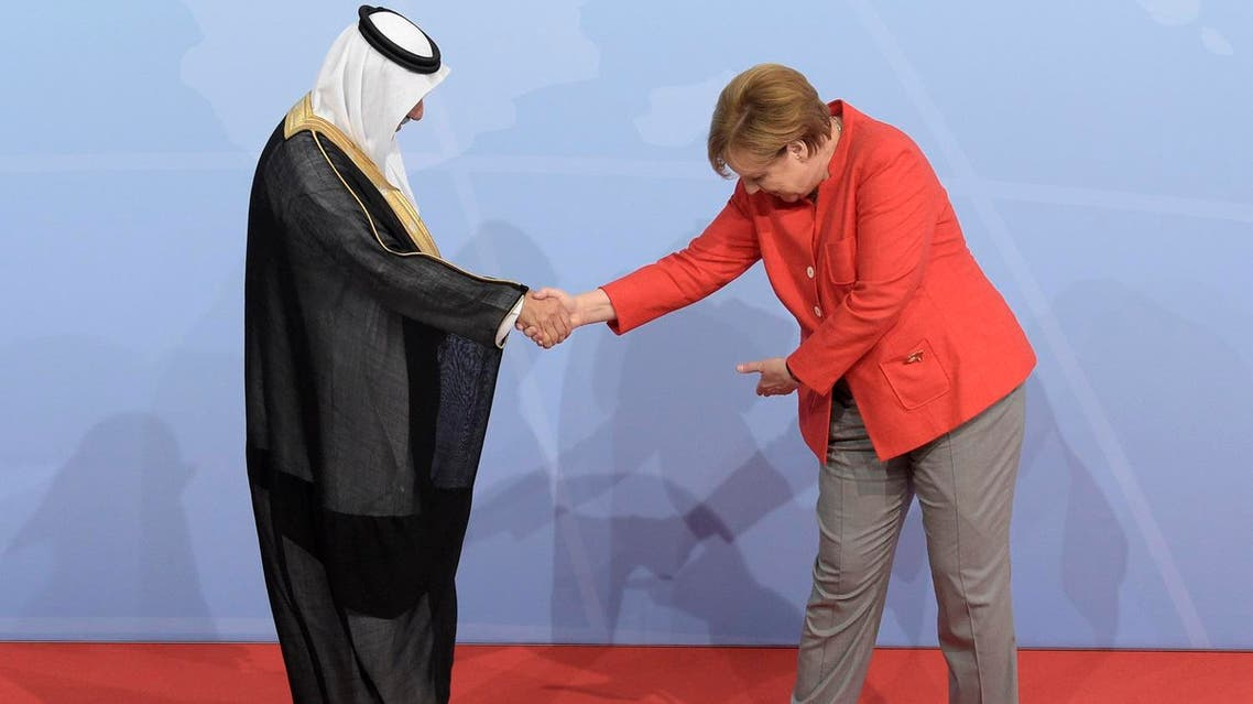 Saudi Arabia's State Minister Ibrahim al-Assaf is welcomed by German Chancellor Angela Merkel on the first day of the G-20 summit in Hamburg, on July 7, 2017. (AP)