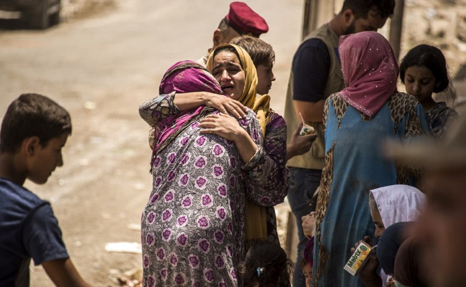 An Iraqi woman, who fled the fighting between government forces and ISIS militants in the Old City of Mosul, reacts while embracing another in the city's western industrial district as they wait to be relocated, on July 8, 2017. (AFP)