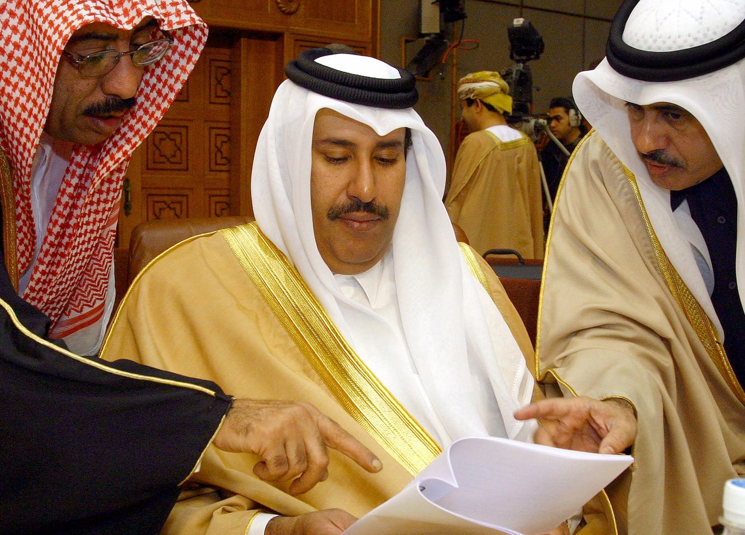 Qatar Foreign Minister Sheikh Hamad Bin Jasim (C) listens to his aides before a meeting at the Arab League headquarters in Cairo, January 13, 2005. (Reuters)