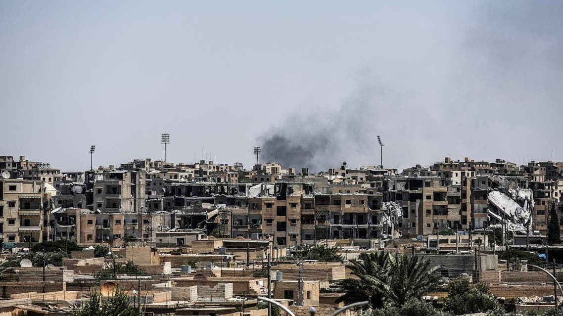 Damaged buildings are seen in western Raqa on July 12, 2017, during an offensive by Syrian Democratic Forces (SDF), an alliance of Kurdish and Arab fighters, to retake the city from Islamic State (IS) group fighters. The US-backed coalition has captured around 30 percent of Raqa city since it entered the IS bastion in June after a months-long operation to capture territory in the surrounding province. (AFP)