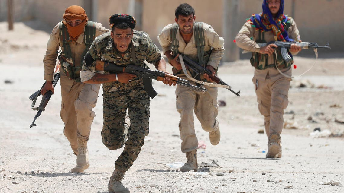 Kurdish fighters from the People's Protection Units (YPG) run across a street in Raqqa, Syria July 3, 2017
